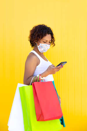 Girl wearing a face mask walking around with her shopping bags and looking at her smartphone. Yellow background. Space for text. New normal concept.