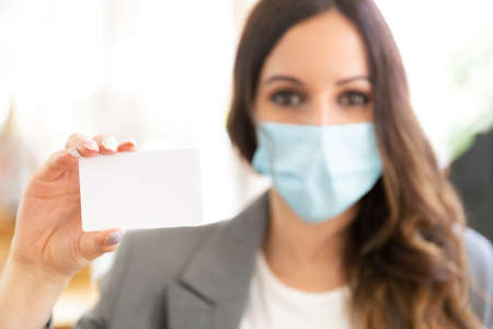 Female executive showing a blank credit card at the office. She's wearing a face mask and formal wear. Selective focus. Space for text. Business and new normal concept.