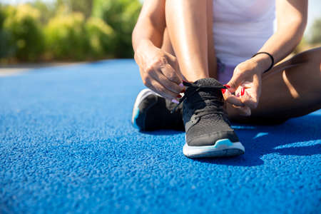 Close-up of a sportswoman tying her shoe laces before running. Space for text. Selective focus. Concept of sport and healthy life.