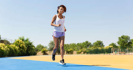Brunette woman running enthusiastically on the track. Space for text. Concept of healthy life.