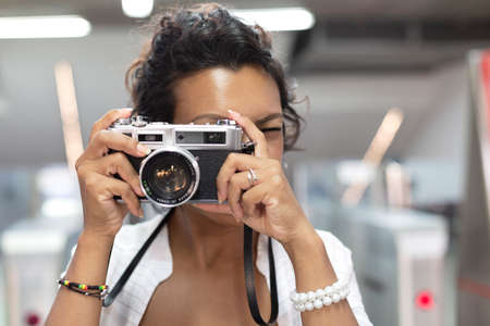 Close-up of a woman with exotic features taking a picture with an analog film camera. Selective focus. Concept of travel and tourism.