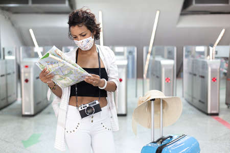 Traveling woman with a face mask looking at a tourist map. She's standing next to a travel bag. New normal travel after covid-19 pandemic concept.