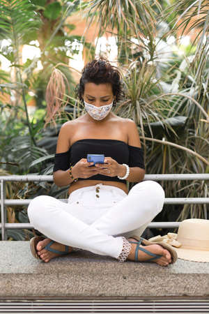 Young brunette woman using her cell phone. She is sitting next to some plants and is wearing a face mask. Concept of new normal in public spaces.