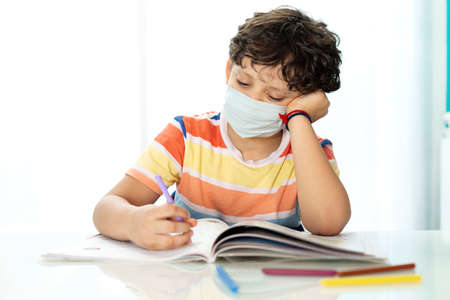 Little boy studying. He is wearing a face mask. Concept of education in period of new normal.