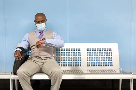Black businessman looking at the time on his watch. He is sitting on a bench in the subway station and is wearing a face mask. Space for text. 免版税图像