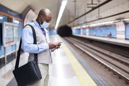 Black man wearing a face mask using his smartphone inside a subway station. Safe travel and new normal during the Covid-19 pandemic.