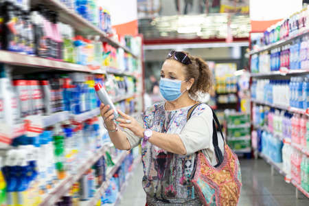 Older woman looking at a product inside the supermarket. She is wearing a medical mask. Stok Fotoğraf