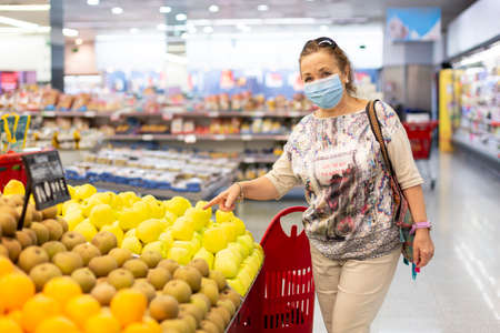 Smiling woman pointing to a few apples inside the supermarket. She is wearing a face mask. Space for text.