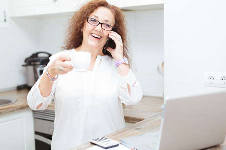 Mature woman smiling on the phone while holding a cup of coffee. She is in the kitchen next to a laptop and other gadgets. Stockfoto