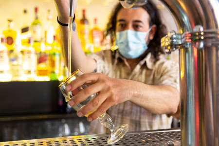 Close up of a barman wearing a medical mask filling a beer glass in a modern bar. Concept of new restrictions in nightlife. Selective focus.