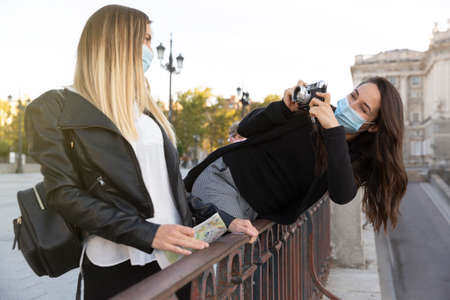 A girl taking a picture of her friend with an analog camera. Both are wearing face masks. Concept of new normal.