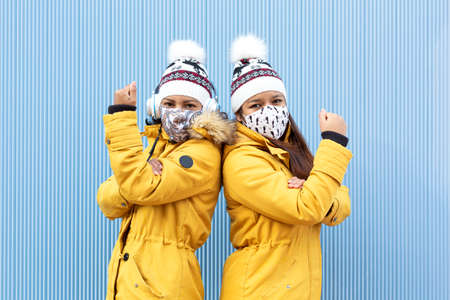 Two people wearing face masks and winter clothes isolated on a blue background. They are doing with their arms a gesture of force. Concept of the fight against the Covid-19 virus pandemic.