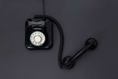 Top view of 1960 's retro telephone isolated on a black background. Space for text. Communication concept.