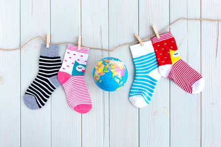 Children's socks with stripes and colors in clothesline on wooden background. In the center is a globe of the world. World Down Syndrome Day concept.