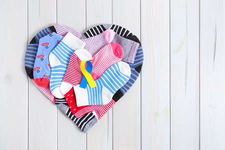 Heart formed by different striped and colored children's socks on a wooden background. In the center there is a yellow and blue ribbon. World Down Syndrome Day concept.