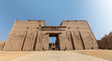 The main entrance of Edfu Temple showing the first pylon, Dedicated to the Falcon God Horus, Located on the west bank of the Nile, Edfu, Upper Egypt 新聞圖片