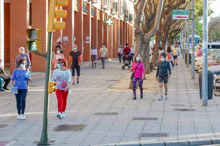 Huelva, Spain - May 5, 2020: People going out for a walk wearing protective or medical face masks during the alarm state and quarantine in Spain.
