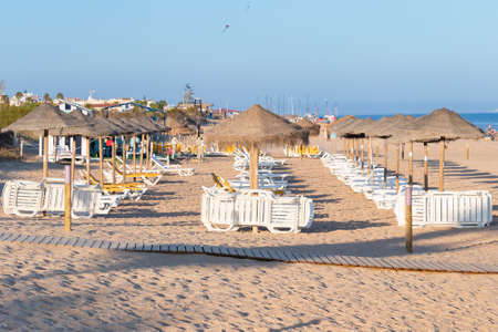 Sun umbrellas and hammocks in row for rent for tourist in Islantilla beach