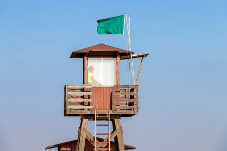 A lifeguard sitting on surveillance tower at sunset. Red wooden lifeguard tower