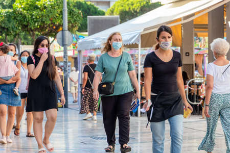 Punta Umbria, Huelva, Spain - July 10, 2020: Two women walking by street wearing protective mask due to covid-19. New normal in Spain Editorial