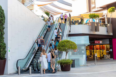 Huelva, Spain - July 27, 2020: People at automatic stairs of Holea Shopping center wearing protective mask due to coronavirus covid-19. New normal in Spain