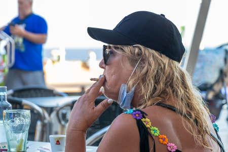 Huelva, Spain - July 10, 2020: Mature blond woman wearing face mask to avoid covid-19 coronavirus is smoking a cigarette in a bar terrace