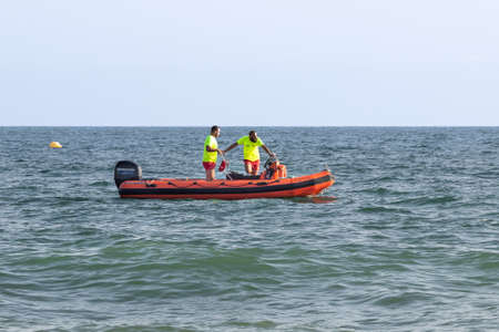 Punta Umbria, Huelva, Spain - August 7, 2020: Rescue boat that slowly sail by the coast. Motor boat and rescuers. The boat has emergency equipment and medicines, life jackets.