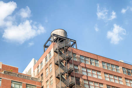 Water towers or rooftop Water Tank on an Apartment Building with Fire Escape stairs in New York. Deposits typical of a rooftop in the city of New York, USA.