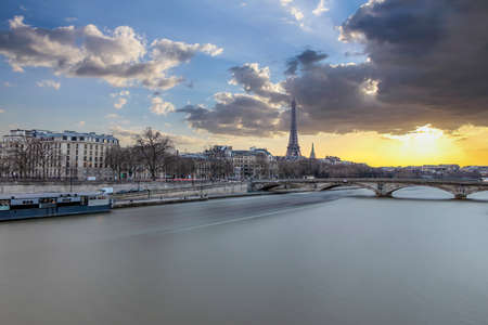 Long exposure photography of sunset in Paris in a cloudy day, with Seine river and Eiffel tower 写真素材