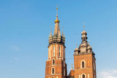 Detail of domes of Gothic Saint Mary Basilica in city center of Krakow, Poland, at evening with Swallows flying
