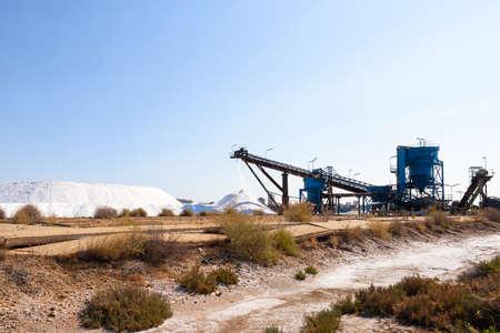 Salt production, conveyor belt with marine salt produced by the evaporation of seawater.