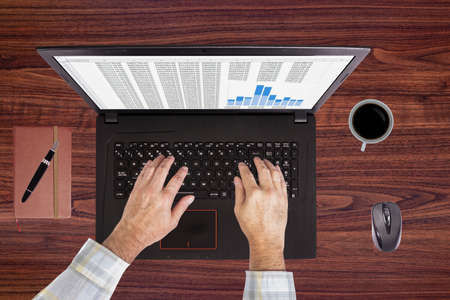 Using laptop with a cup of coffee Stock Photo