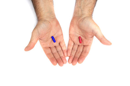 Red and blue pills on hand isolated on white background. They represent the choice between embracing the truth and reality, red or blissful ignorance, blue Stock fotó
