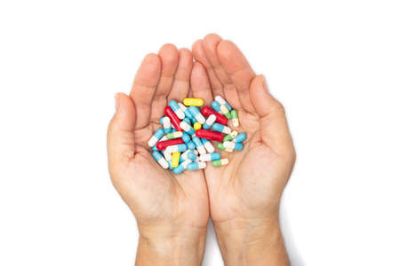 A handful of colored pills in the hands Stock fotó