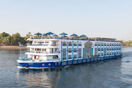 Aswan, Egypt - September 16, 2018: Floating hotel (tourist boat) motor down the River Nile towards Aswan in central Egypt. The tourist boats cruise between Luxor and Aswan in Upper Egypt