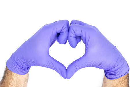 Hands of a doctor or nurse with medical gloves depict a heart isolated on a white background, medicine concept Stock fotó