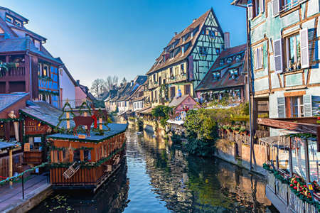 Colmar, France - december 1,2019: Traditional Alsatian half-timbered houses and river Lauch in Petite Venise or little Venice, old town of Colmar, decorated at christmas time, Alsace, France