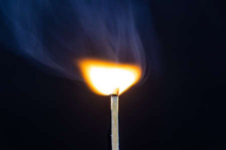 Single matchstick start on fire isolated on black background