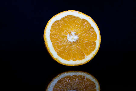 Orange cut in half isolated on black background