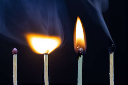 Matchstick on fire and extinguished isolated on black background
