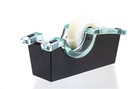 Clear tape dispenser isolated on a white background. Tape dispenser that sits firmly on a desk or similar surface