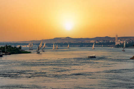 View of a beautiful orange sunset in Aswan, Egypt with a lot of felucca sailing in the Nile river Stockfoto