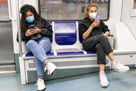 Barcelona, Spain - September 21, 2021: Two young women use their mobile phones while riding the metro. They are wearing a protective face mask due to the coronavirus covid-19 epidemic