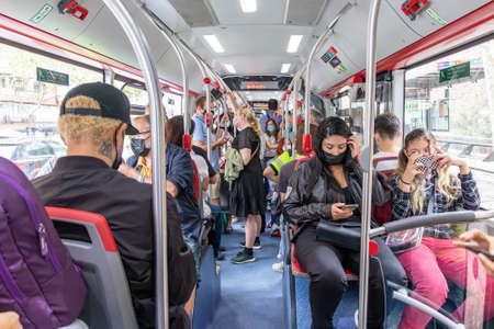 Barcelona, Spain - September 24, 2021: Crowds of people inside a bus. Interior view of a municipal bus with passengers wearing protective mask and different people sitting on the seats