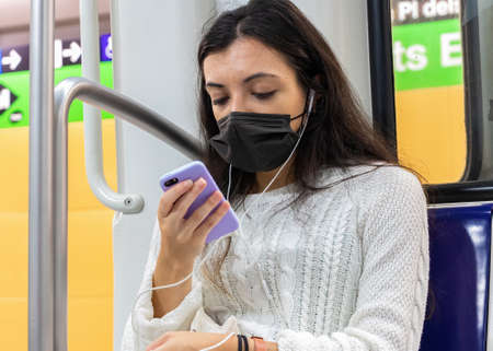 Barcelona, Spain - September 21, 2021: A young woman is using her mobile phone while is traveling in the subway. She is using a protective face mask due to coronavirus covid-19 epidemic Redactioneel