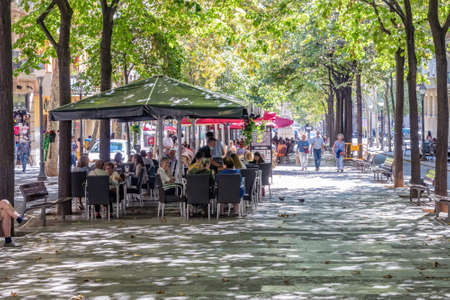 Barcelona, Spain - September 19, 2021: View of Some people walking along the Ramblas in Barcelona (boulevard) and others having a drink on the terrace of a bar, in Barcelona, Catalonia, Spain Redactioneel