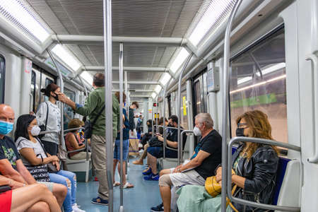 Barcelona, Spain - September 24, 2021: Crowds of people inside the subway. Interior view of a metropolitan train with passengers wearing protective mask and different people sitting on the seats