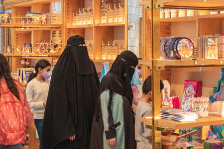 Barcelona, Spain - September 19, 2021: Muslim women wearing a Burka, traditional clothing worn by women in some Islamic countries, are shopping in a souvenir shop