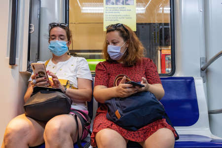 Barcelona, Spain - September 21, 2021: Two women are using her mobile phone while is travelling in the subway. They are using a protective face mask due to coronavirus covid-19 epidemic