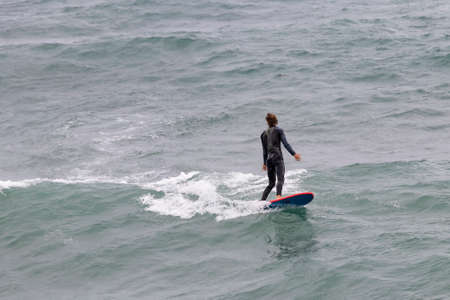 wetsuit surfer catching a wave